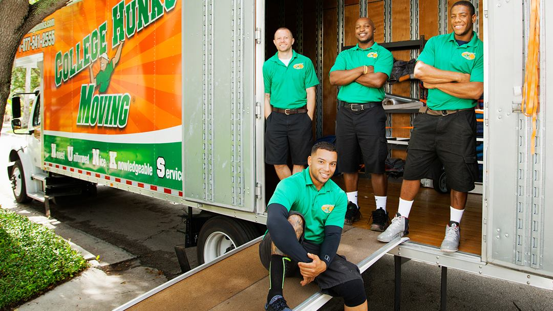 Four College Hunks Hauling Junk employees posing near their truck